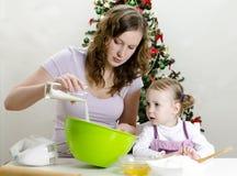 La niña y la madre están preparando las galletas Fotos de archivo libres de regalías