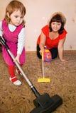La niña y la mujer limpian una alfombra con la aspiradora Fotos de archivo libres de regalías