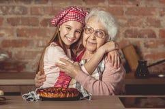 La nieta abraza a su abuela feliz Imágenes de archivo libres de regalías