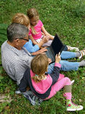 La nieta enseña al abuelo en la computadora portátil Foto de archivo libre de regalías