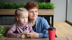 La nieta insert? los auriculares en los o?dos de su abuela almacen de video