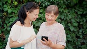 La nieta muestra a vieja abuela algo en smartphone, le enseña a dirigir con el artilugio moderno y la tecnología almacen de video