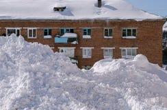 La nieve acumulada por la ventisca miente delante de la casa del ladrillo Fotografía de archivo libre de regalías