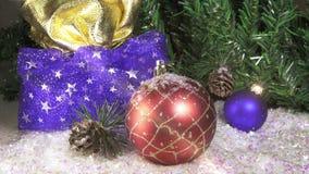 La nieve cae lentamente en bolas del ` s del Año Nuevo contra la perspectiva de un abeto de la Navidad Cámara lenta almacen de metraje de vídeo