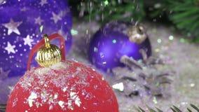 La nieve cae lentamente en bolas del ` s del Año Nuevo contra la perspectiva de un abeto de la Navidad Cámara lenta almacen de video