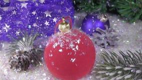La nieve cae lentamente en bolas del ` s del Año Nuevo contra la perspectiva de un abeto de la Navidad Cámara lenta metrajes