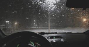 La nieve cae sobre el vidrio y los derretimientos del coche en la noche Visi?n interior metrajes