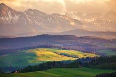 La nieve caped las montañas y los campos y los prados verdes fotografía de archivo libre de regalías