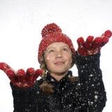 La nieve de cogida de la muchacha feliz forma escamas en su mano Foto de archivo libre de regalías