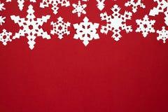 La nieve de papel forma escamas en el fondo rojo Tema del rojo de la Navidad Imagen de archivo libre de regalías