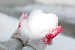La nieve del asimiento de las manos tiene gusto de un corazón Fotos de archivo libres de regalías