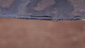 La nieve derrite y el agua cae el goteo del tejado viejo de la casa almacen de metraje de vídeo
