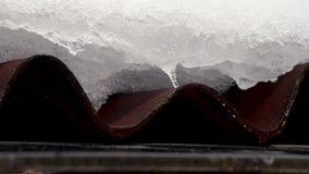 La nieve derrite y el agua cae el goteo del tejado viejo de la casa almacen de video