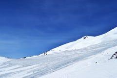 La nieve enarbola, canto, cielo azul, flotando las nubes hermosa vista de la cuesta del esquí Fotos de archivo