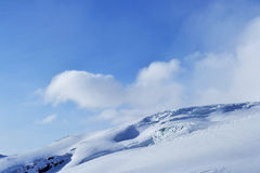 La nieve enarbola, canto, cielo azul, flotando las nubes hermosa vista de la cuesta del esquí Imágenes de archivo libres de regalías