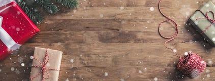 La nieve forma escamas cayendo sobre los regalos en una tabla-bandera de madera con el espacio de la copia Imagen de archivo libre de regalías