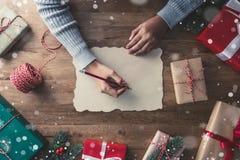 La nieve forma escamas cayendo sobre los regalos en una tabla-bandera de madera con el espacio de la copia Imágenes de archivo libres de regalías