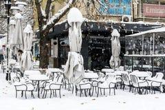 La nieve llena para arriba en las tablas y las sillas en una barra de café Foto de archivo libre de regalías