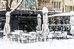 La nieve llena para arriba en las tablas y las sillas en una barra de café Fotografía de archivo