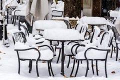 La nieve llena para arriba en una tabla y sillas Foto de archivo