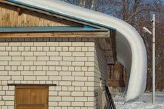 La nieve resbala abajo del tejado Imagen de archivo