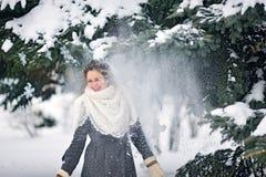 La nieve vuela en una muchacha en el parque en invierno Imagenes de archivo