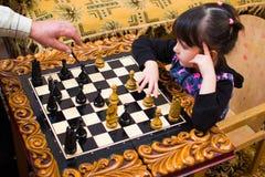 La nipote gioca gli scacchi con suo nonno il nonno insegna a per giocare immagine stock