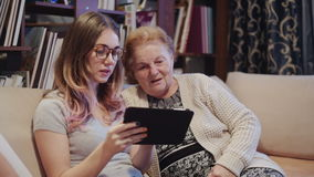 La nipote gode mostrare adella sua nonna come utilizzare il nuovo PC della compressa stock footage