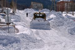La niveladora limpia la calle, de la nieve en el pueblo Foto de archivo libre de regalías