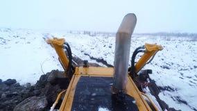 La niveladora y el excavador trabajan a máquina el trabajo con la tierra el día de invierno de la nieve Visión desde la cabina metrajes