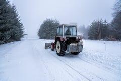 La niveleuse rouge de souffleuse de neige dégage la route couverte par neige de station de sports d'hiver photographie stock