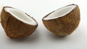 La noce di cocco tropicale matura ha spaccato a metà due che girano su un fondo bianco Frutta tropicale collegato archivi video