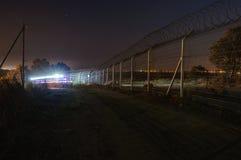 La noche, coche patrulla de la seguridad emerge de la curva del rastro Imagenes de archivo