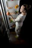 La noche de la muchacha fuera del refrigerador saca Apple Fotografía de archivo
