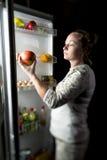 La noche de la muchacha fuera del refrigerador saca Apple Imágenes de archivo libres de regalías