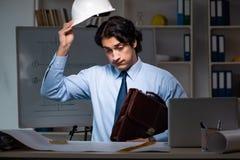 La noche de trabajo del arquitecto de sexo masculino joven en la oficina imágenes de archivo libres de regalías