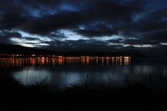 La noche enciende la ciudad de la playa en Islandia Imagenes de archivo