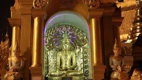 La noche tirada de la estatua de Buda del estuco adornada en de oro se engarce dentro del arco en la pagoda de Shwedagon, Rang?n almacen de video