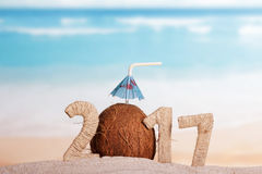 La noix de coco numéro à la place 0 en 2017 en sable contre la mer Image libre de droits