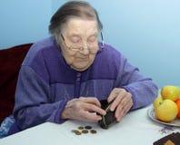 La nonna anziana alla tavola pensa il penny Fotografia Stock