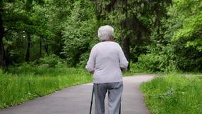 La nonna cammina nel parco con i bastoni per nordico che cammina nel pensionamento video d archivio