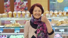 La nonna compra il pane fresco al supermercato, lei mostra il suo pollice su stock footage