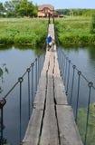 La nonna con una bicicletta e le borse sono sul ponte sospeso sopra il fiume Immagine Stock Libera da Diritti