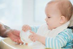 La nonna dà gli alimenti per bambini da un cucchiaio Fotografia Stock Libera da Diritti