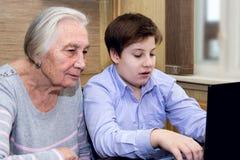 La nonna del nipote insegna all'alfabetizzazione informatica Fotografie Stock Libere da Diritti