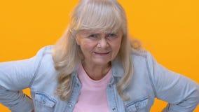 La nonna deludente che guarda irosamente sul fondo giallo, vecchia generazione, accusa stock footage