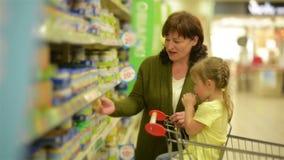 La nonna e la nipote stanno comprando gli oggetti al centro commerciale La nipote sta sedendosi in carrelli di acquisto video d archivio