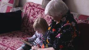 La nonna e la nipote stanno sedendo sul sofà stock footage