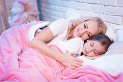 La nonna e la nipote stanno trovando a letto alla notte a casa fotografie stock