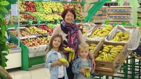 La nonna ed i nipoti comprano le banane nel deposito Movimento lento stock footage